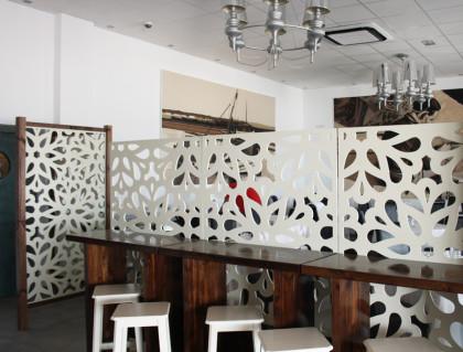 celosias de madera pintadas en blanco, para separación de ambientes en restaurante