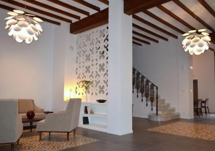 Separador de ambientes en el hall de entrada de un hotel, fabricado con celosias de madera y acabado pintado en blanco